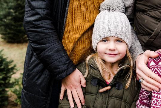 portrait little girl in big woolly hat in Christmas tree farm