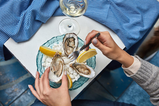 The girl's hands hold a fork and an open fresh oyster on the background of plates with lemon slices, oysters and a glass of wine on the table with a blue tablecloth. Dinner at the restaurant