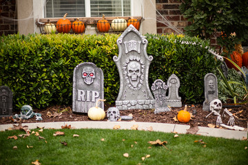 Exterior view of home decorated with Halloween decorations. Skeletons and tombstones and pumpkins cover the front yard of a home.