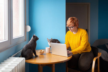 Young blond woman using her laptop at home