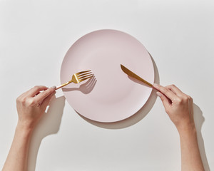 Waiting for oder dinner with served plate, fork and knife in a girl's hands on a white background. Place for text, top view.