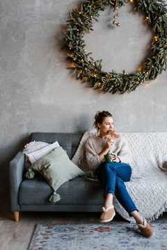 Woman having cookie on sofa in Xmas time