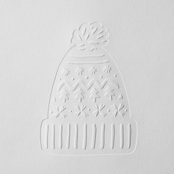 Embossed pattern on a gray cardboard in the form of a hat decorated with snowflakes and Christmas trees with copy space. Layout for Christmas card. Top view