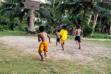 Asian kids playing basketball in the jungle
