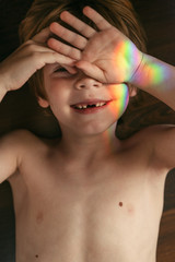 Portrait of shirtless boy with rainbow glare on his face