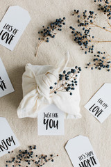 Privet branches with berries and gift cards surround a present wrapped inside cotton napkin