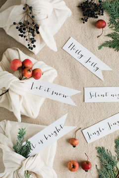 CHristmas greetings handwritten on tags close to gifts wrapped inside cotton napkins and decorated with botanical elements