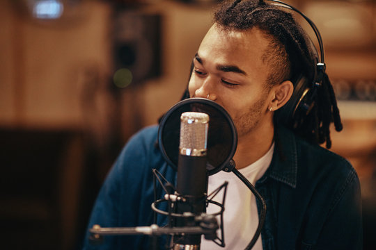 Young man singing during a studio recording session