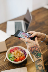 Woman taking picture of poke bowl in cafe