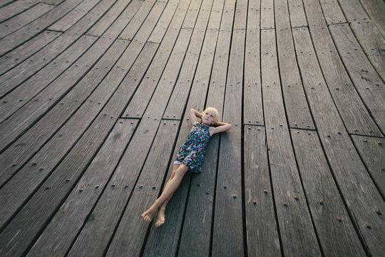 Little girl lying on wooden floor
