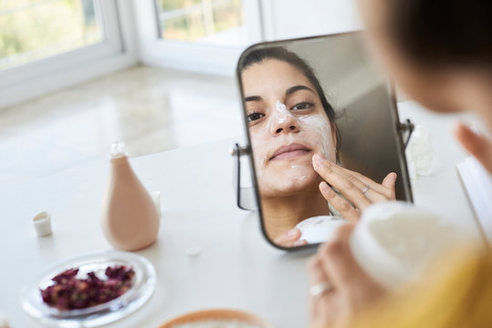 Mirror reflection woman applying skincare mask.