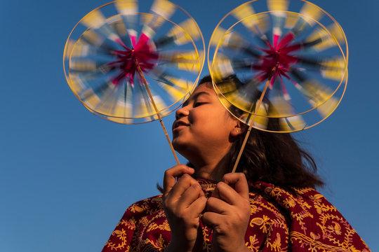 Teenage girl playing with pinwheels against sky