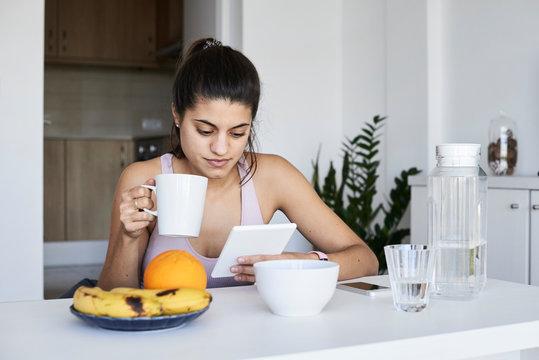 Sportswoman having breakfast and reading.