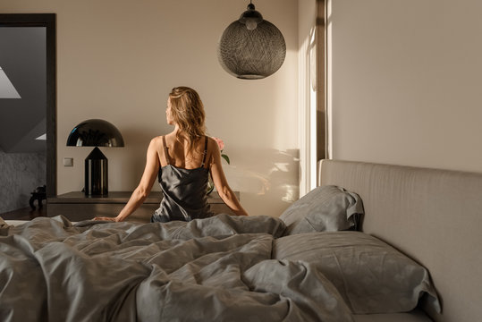 Woman sitting on bed in morning sunlight