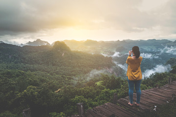 Woman traveler take a photo of sunrise with beautiful moutain scenes in Ban Cha Bo, Mhong Mountaineer village the north of Thailand, Inspiration concept