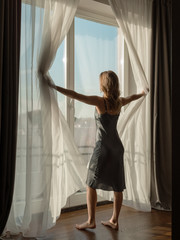 Dreamy woman opening curtains in morning