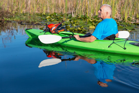 Senior citizen male takes a break from paddling and drifts in a green kayak on a marshy lake in Florida.