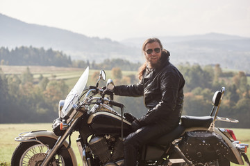 Handsome bearded motorcyclist with long hair in black leather jacket and sunglasses sitting on cruiser motorcycle, on blurred background of green peaceful rural landscape and light foggy sky.