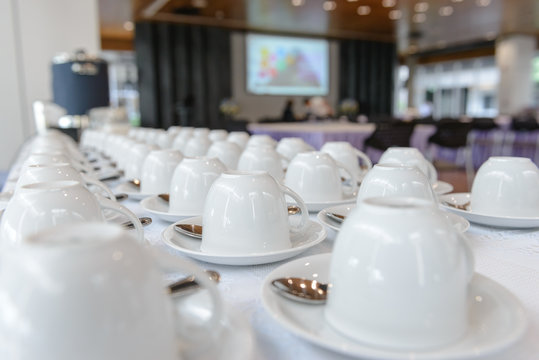 Group of many empty cups with spoons for service coffee or tea in seminar event or meeting room