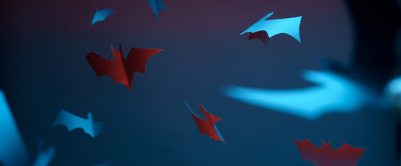 Picture of blue and red paper bats on empty halloween background.