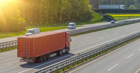 LKW mit Container auf der Autobahn im Sonnenlicht