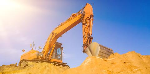 orange farbener Bagger auf der Baustelle Abbruch mit klarem blauem Himmel und Sonnenstrahlen
