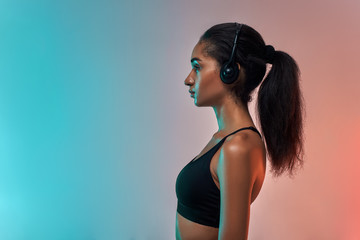 Music for workout. Side view of attractive young athlete woman in headphones standing against colorful background