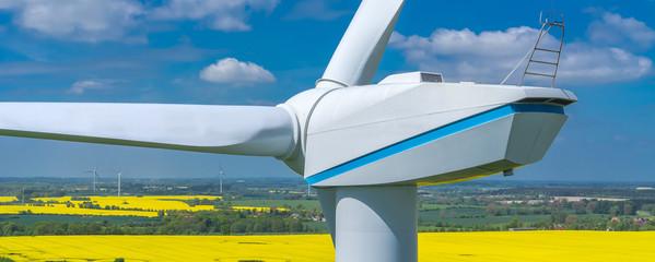 Windkraftanlage im Sonnenlicht mit Raps Feld im Hintergrund Luftbild