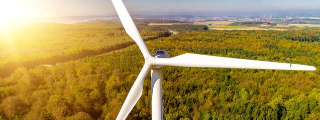 Windkraftanlage im Sonnenlicht im Wald Luftbild