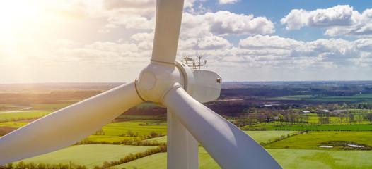 Windkraftanlage im Sonnenlicht vor Feldern Luftbild
