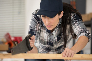focused woman using handsaw