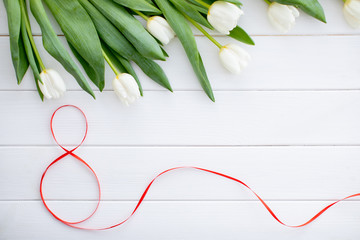Love. Valentines day. Bouquet of tulips on white background with a two red hearts a symbol of the holiday. Spring flowers. Flat lay. Greeting card for March 8 Woman's Day. - Image