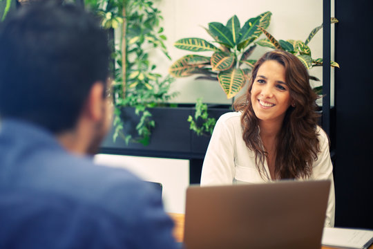 Job interview process in a coworking space by recruiter. Female in her 30s interviewing a male candidate.