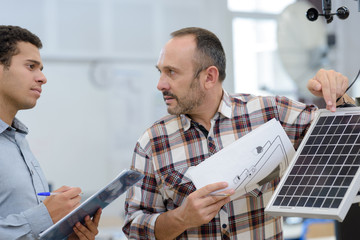 two men with clipboard and instructions for solar panel