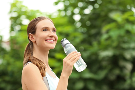 Young woman with bottle of water outdoors. Refreshing drink