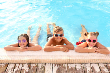 Happy children with sunglasses in swimming pool on sunny day