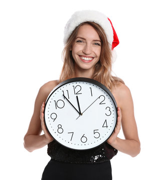 Happy young woman in Santa hat holding clock on white background. Christmas celebration