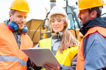 Three workers in a quarry discussing in front of heavy machinery