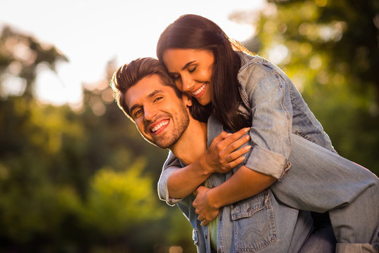Close up photo of attractive married youth cuddling pigyback wearing denim jeans jackets blazers outside in forest