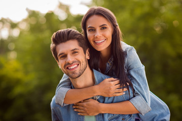 Close up photo of charming couple piggyback wearing denim jeans outdoors