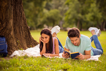Her she his he nice attractive lovely smart clever focused concentrated best friends spending weekend free spare time on fresh open air lying under tree on veil cover outside