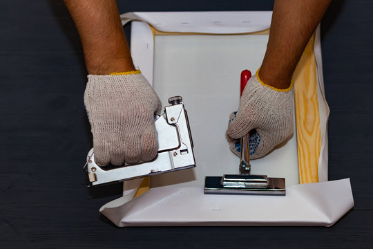 Canvas stretching. Wooden stretcher bar, staple gun, canvas pliers, male hand in white protect glove