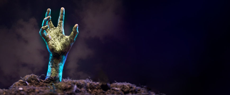 Photo of zombie hand sticking out of grave, black background.