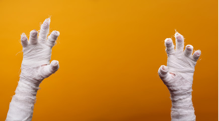 Photo of two mummy hands on empty orange background .