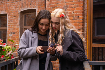 two girls are watching photos on a smartphone