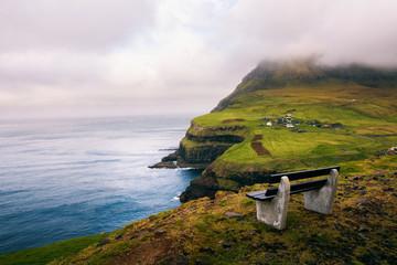 Wall Mural - Bench above Gasadalur village with views over Atlantic Ocean on Faroe Islands