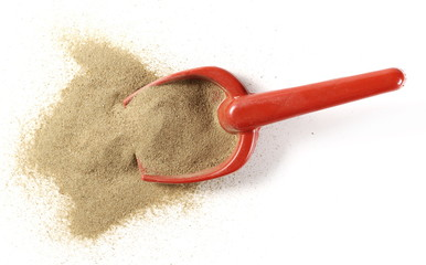 Beach toy for kids, plastic tool in sand pile isolated on white background, top view