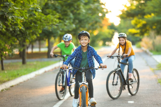 Cute children riding bicycles outdoors