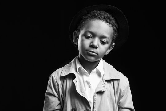 Black and white portrait of sad African-American boy on dark background