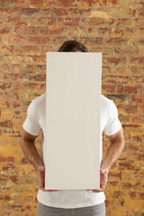 Blank canvas held in front of brick wall